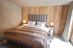 Ski chalet bedroom with plush throw on bed, place against a vertically clad wooden wall